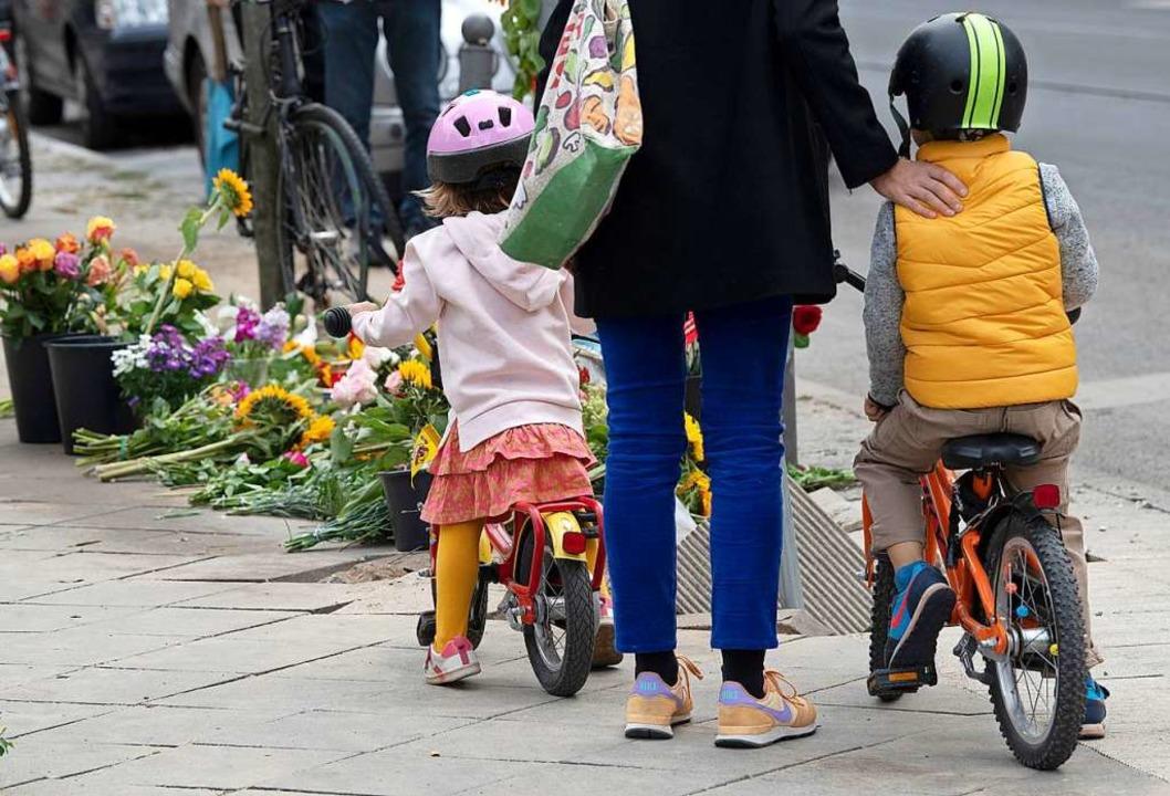 Eine Frau und zwei Kinder stehen an de...Ackerstraße auf einen Gehweg gefahren.  | Foto: Paul Zinken (dpa)