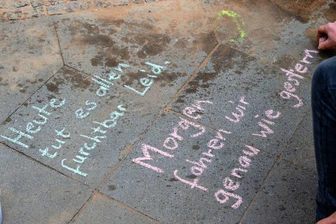 Ein Mann schreibt mit Kreide diese Bot... einem Verkehrsunfall gestorben waren.  | Foto: Paul Zinken (dpa)