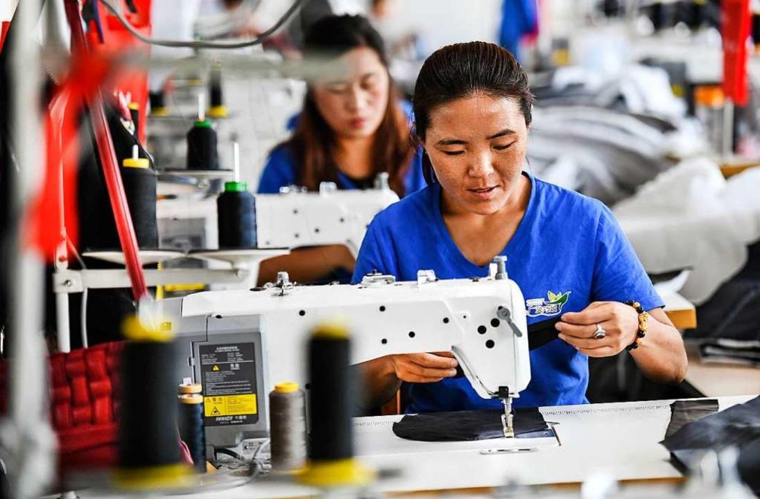 Arbeiterinnen stellen Kleidung in eine...n der Provinz Shanxi in Nordchina her.  | Foto: dpa
