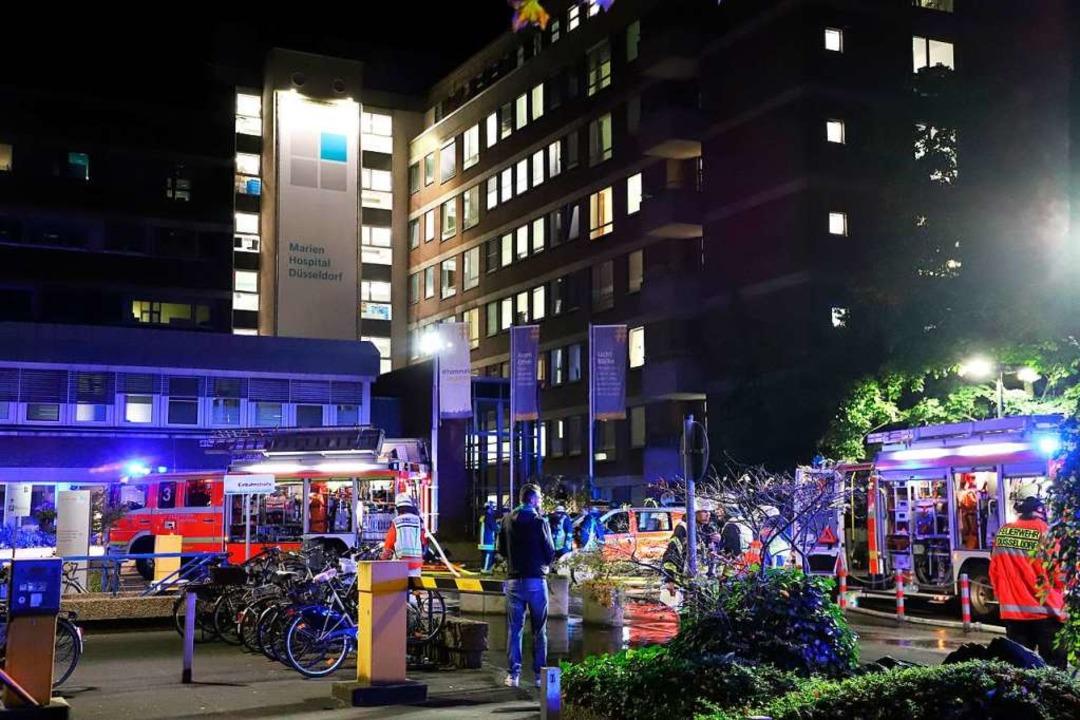 Einsatzkräfte der Feuerwehr stehen nac...men, Dutzende weitere wurden verletzt.  | Foto: Sascha Rixkens (dpa)