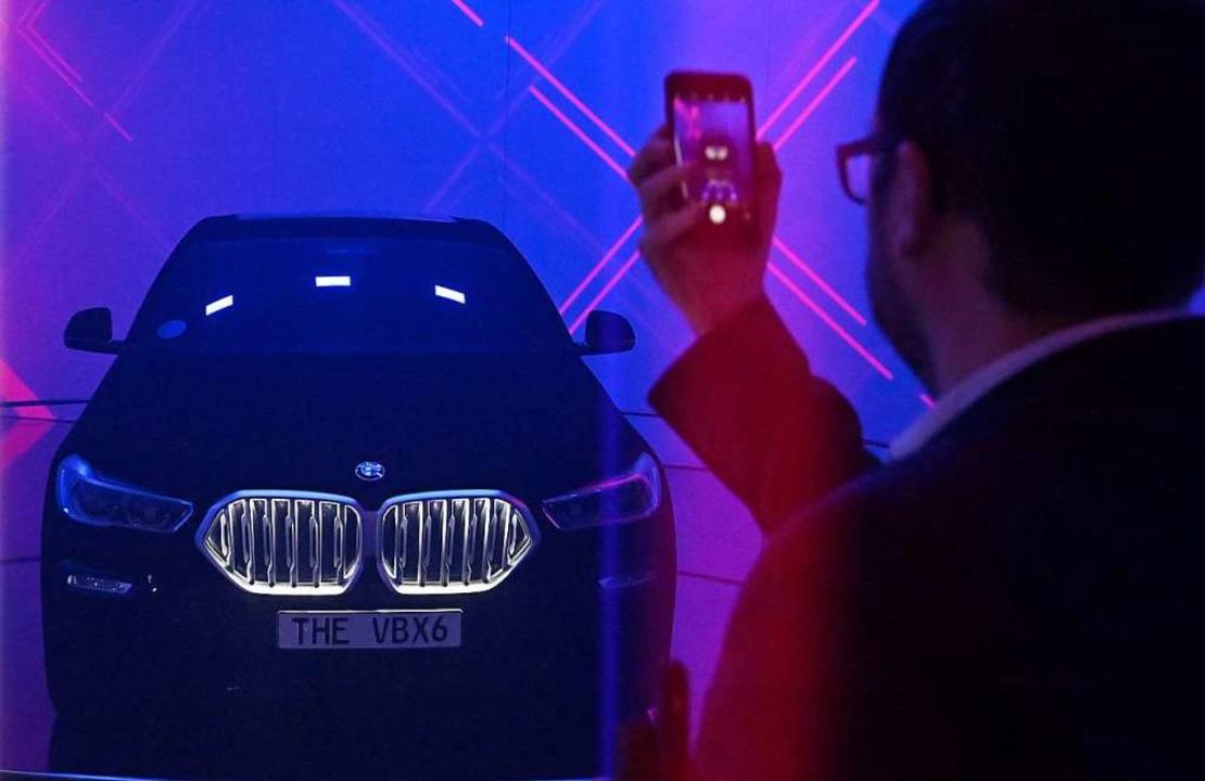 Ein Besucher der IAA macht ein Foto eines BMWs.  | Foto: TOBIAS SCHWARZ (AFP)