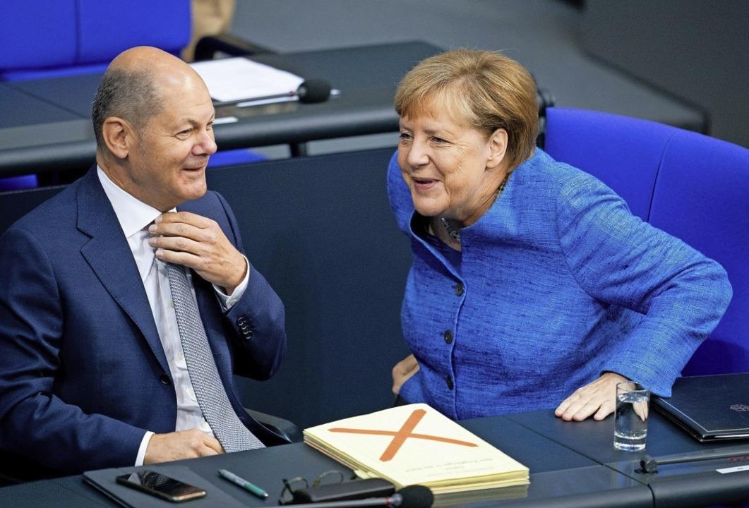 Bundeskanzlerin Angela Merkel (CDU) un...laf Scholz (SPD) scherzen miteinander.  | Foto: Kay Nietfeld (dpa)