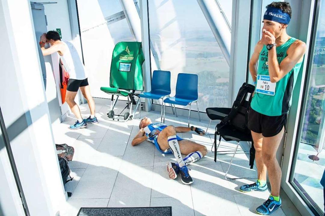 Läufer stehen und liegen erschöpft nac... Rottweiler Testturm von ThyssenKrupp.  | Foto: Sebastian Gollnow (dpa)