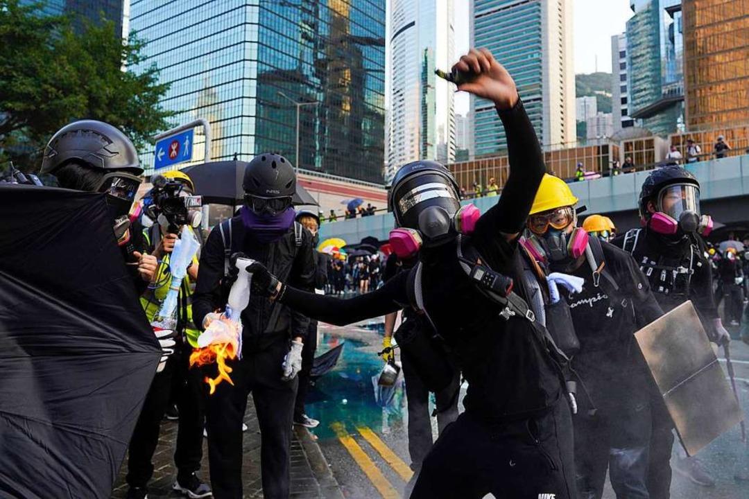 Ein Demonstrant in Hongkong wirft eine...il in der Nähe eines Regierungebäudes.  | Foto: Vincent Yu (dpa)
