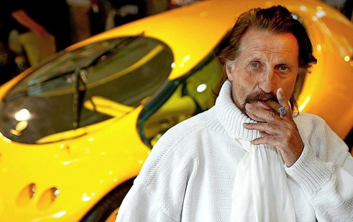 "Lutz ""Luigi"" Colani raucht...hm entworfenen  Experimental-Fahrzeug.  | Foto: Andreas Lander (dpa)"