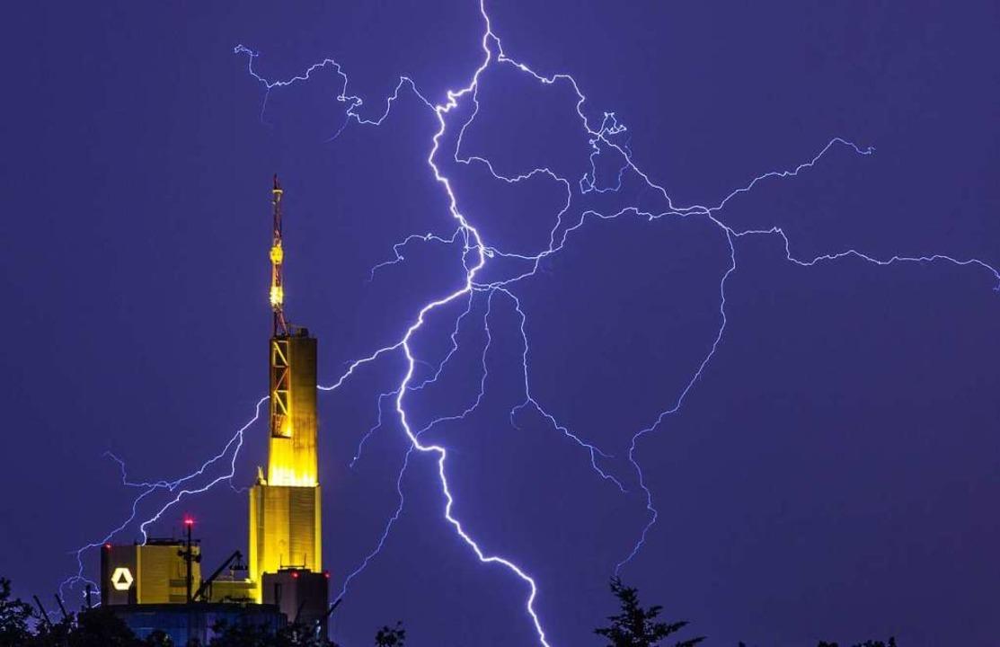Blitze zeichnen sich am nächtlichen Hi...inter der Zentrale der Commerzbank ab.  | Foto: Frank Rumpenhorst (dpa)