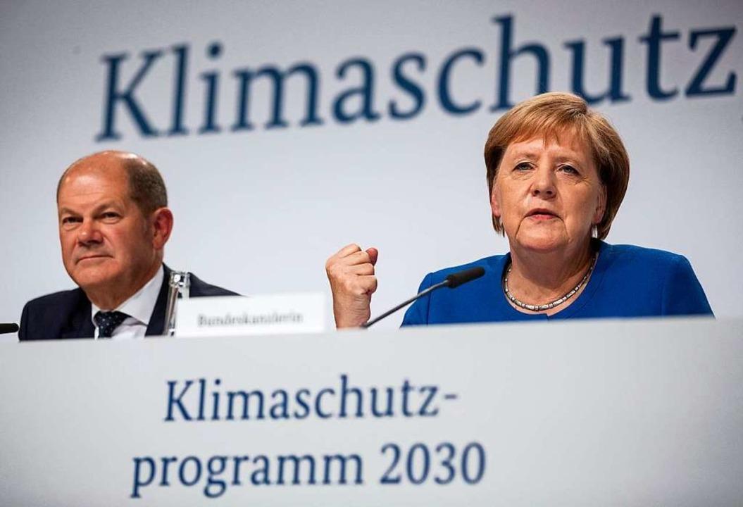 Bundeskanzlerin Angela Merkel (CDU), u...lz (SPD) stellen den Klimareport vor.   | Foto: Christoph Soeder (dpa)