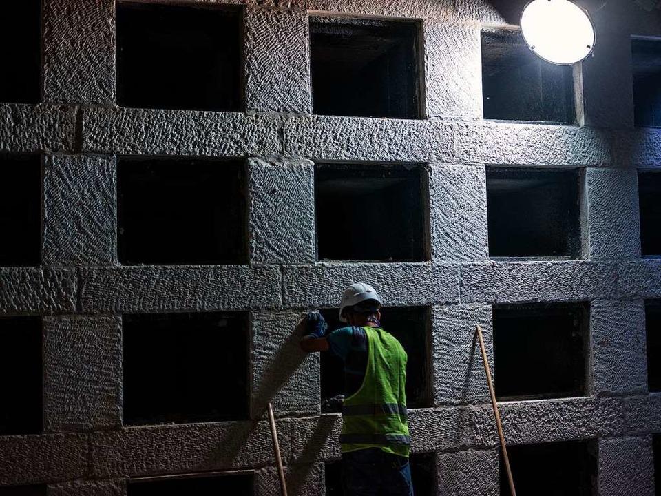 Ein Mann arbeitet während der Bauarbei...ot in einer unterirdischen Grabstätte.  | Foto: Ilia Yefimovich (dpa)