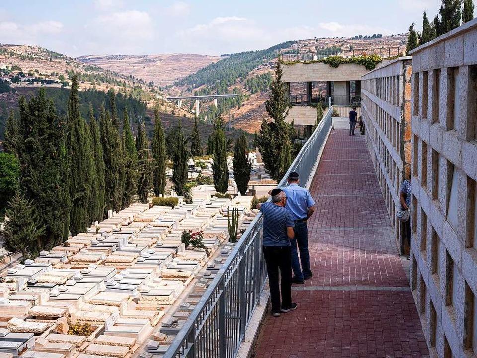 Eine Gesamtansicht zeigt Menschen, die...en Friedhof von Har Hamenuchot stehen.  | Foto: Ilia Yefimovich (dpa)
