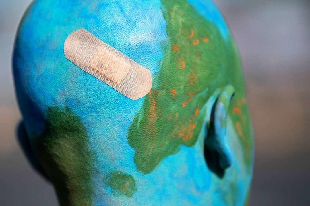 Eine Teilnehmerin der Klimademonstrati...art ist als verletzte Erde geschminkt.  | Foto: Sebastian Gollnow (dpa)