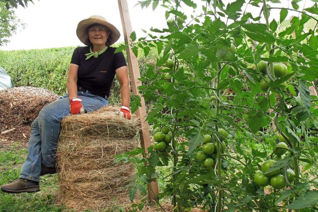 Roswitha Rombach rollt Heuballen aus &...rt als Wasserspeicher für die Tomaten.  | Foto: Jutta Schütz