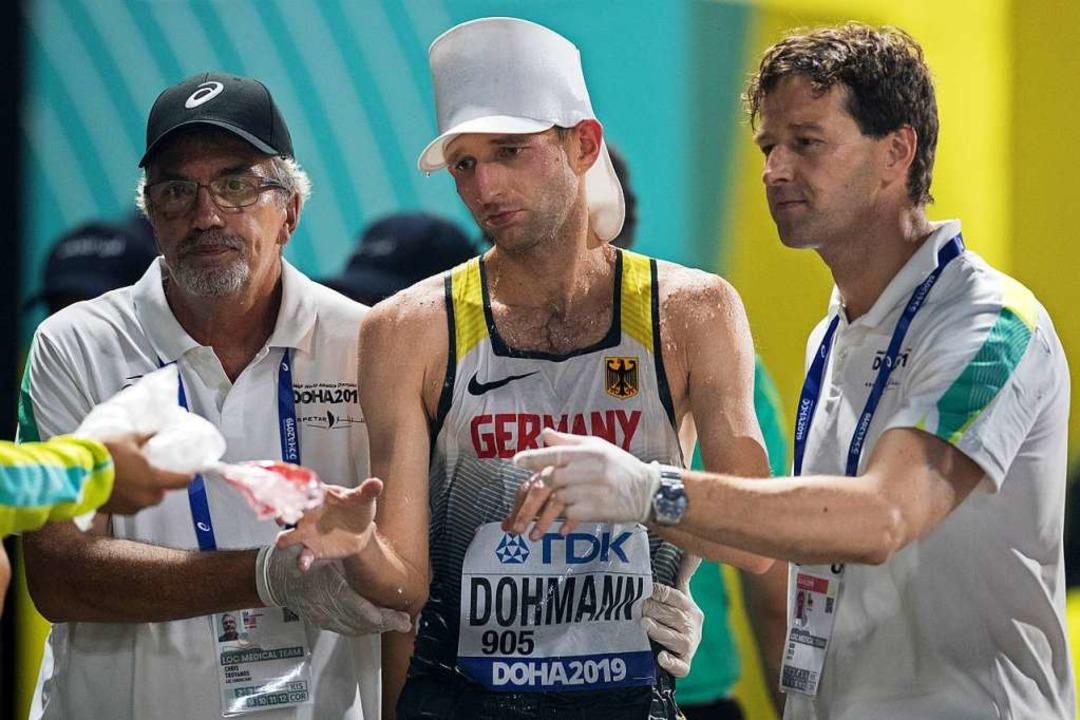 Carl Dohmann wird medizinisch versorgt...er-Nachtwettkampf bei 32 Grad in Doha.  | Foto: Oliver Weiken (dpa)