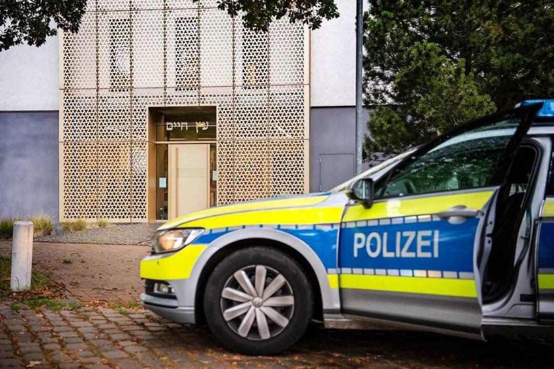 Ein Einsatzfahrzeug der Polizei steht ...ngen für jüdische Gemeinden verstärkt.  | Foto: Sina Schuldt (dpa)