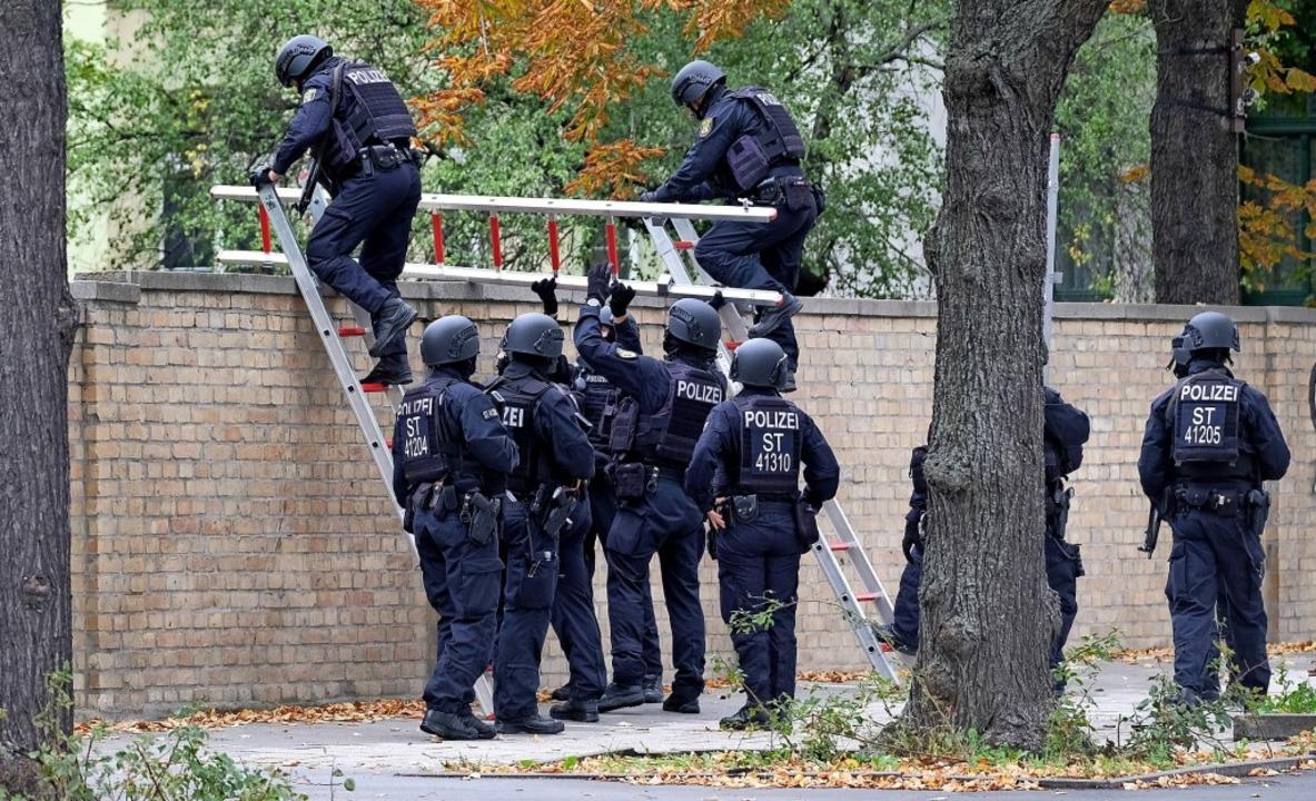 Polizisten mit Schutzhelmen übersteige... Mauer am jüdischen Friedhof in Halle.  | Foto: Sebastian Willnow (dpa)