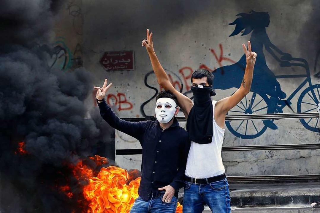 Zwei Männer gestikulieren vor einem br...n die wirtschaftliche Lage des Landes.  | Foto: Bilal Hussein (dpa)