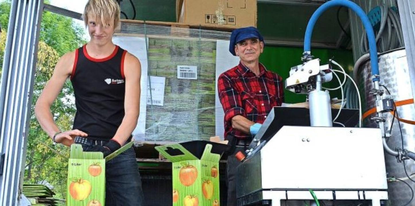 Markus Schütterle (rechts) füllt mit seinem Mitarbeiter die Früchte ab.   | Foto: Gabriele Hennicke