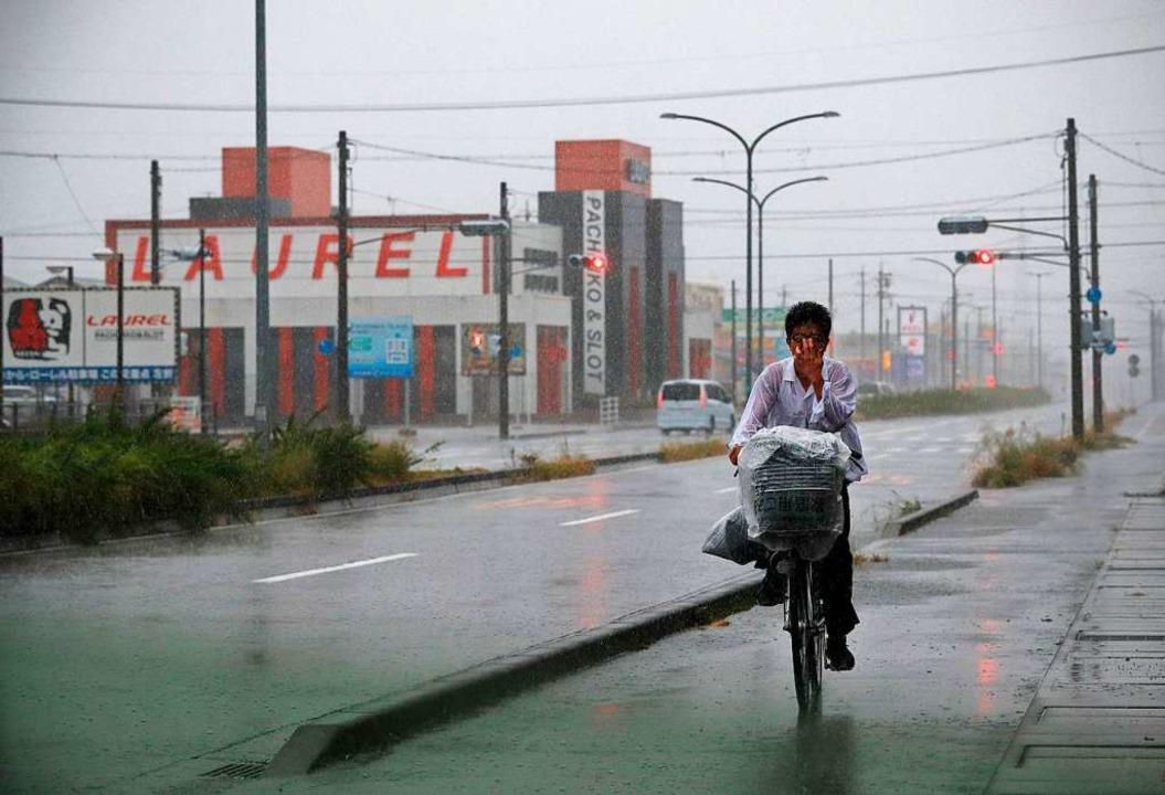 In der Provinz Shizuoka, wo dieser Rad...anden Straßen und Häuser unter Wasser.    Foto: ADRIAN DENNIS (AFP)