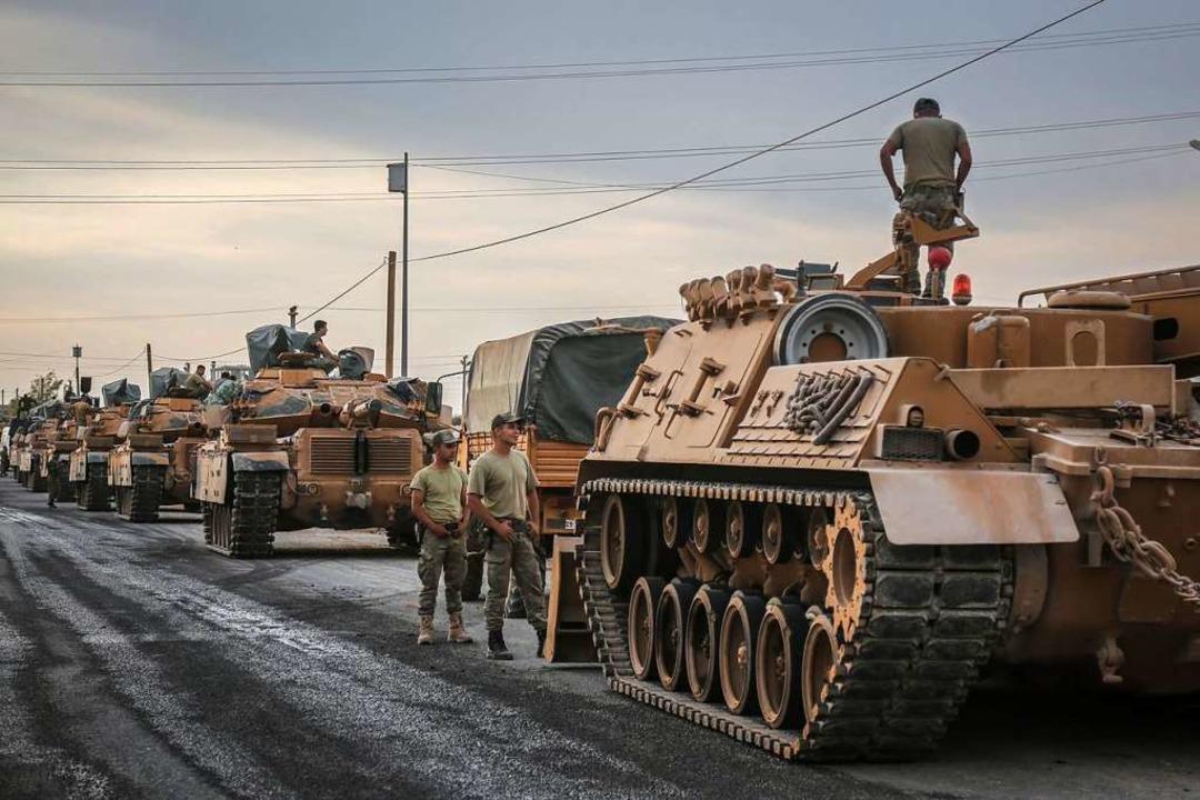 Soldaten und die Militärfahrzeuge steh...onalarmee und warten auf ihre Einsatz.    Foto: Anas Alkharboutli (dpa)