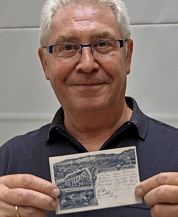 Martin Volk mit einer historischen Ansichtskarte aus Wyhlen.  | Foto: Horatio Gollin