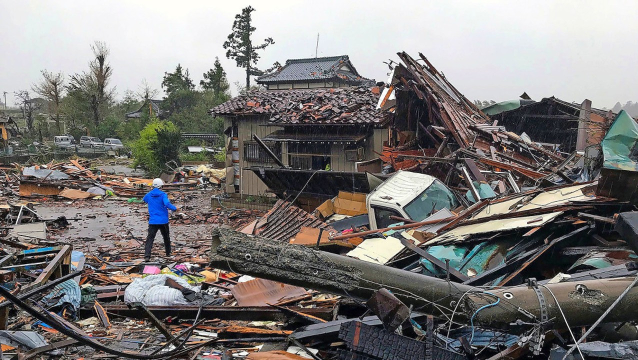 Ein Mann steht vor einem zerstörten Haus in der  japanischen Präfektur Chiba.   | Foto: JIJI PRESS (AFP)