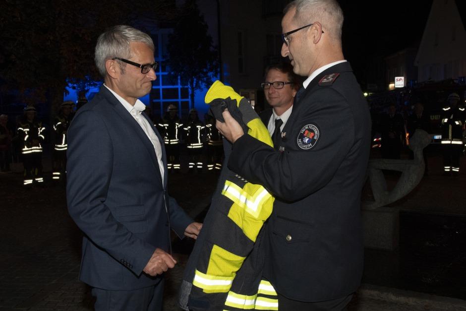 Der neue Bürgermeister Martin Löffler bekommt die Feuerwehrmontur übergestreift. (Foto: Volker Münch)