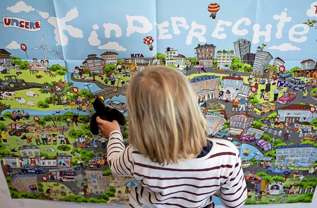 Ein Kind vor einem großen Poster zu Kinderrechten  | Foto: Christoph Soeder (dpa)