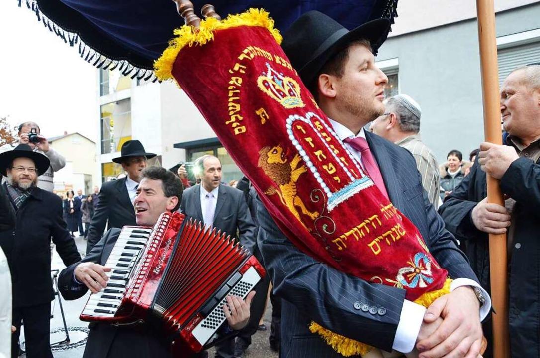 Die jüdische Gemeinde in Lörrach feier... Rabbiner Flomenmann trägt sie im Arm.  | Foto: Barbara Ruda