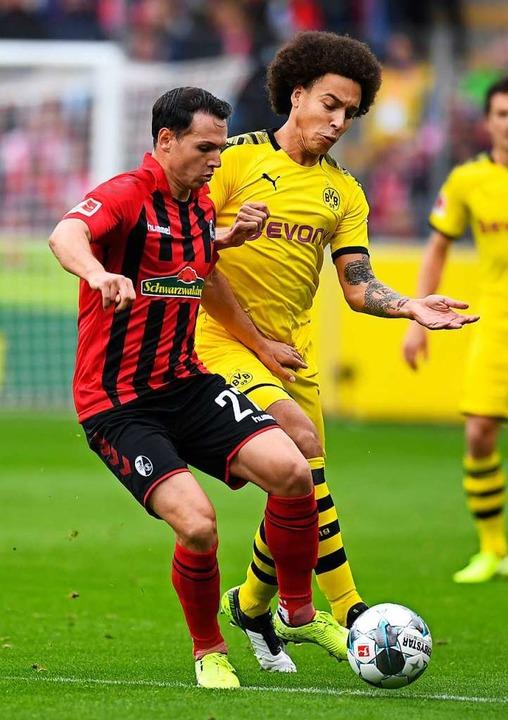 Machte beim 2:2 gegen Dortmund eine gu...Zweikampf mit BVB-Spieler Axel Witsel.  | Foto: THOMAS KIENZLE (AFP)