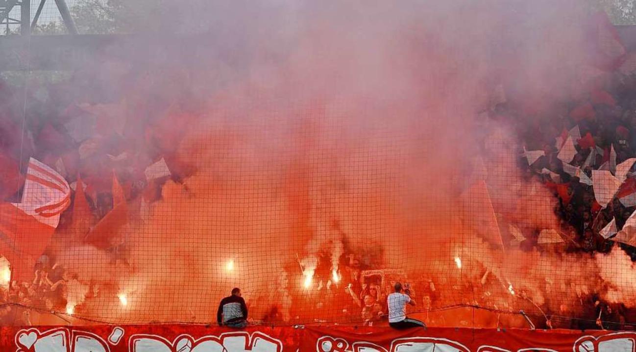 Bengalo-Flammen in der Freiburger Kurve in Berlin.  | Foto: JOHN MACDOUGALL (AFP)