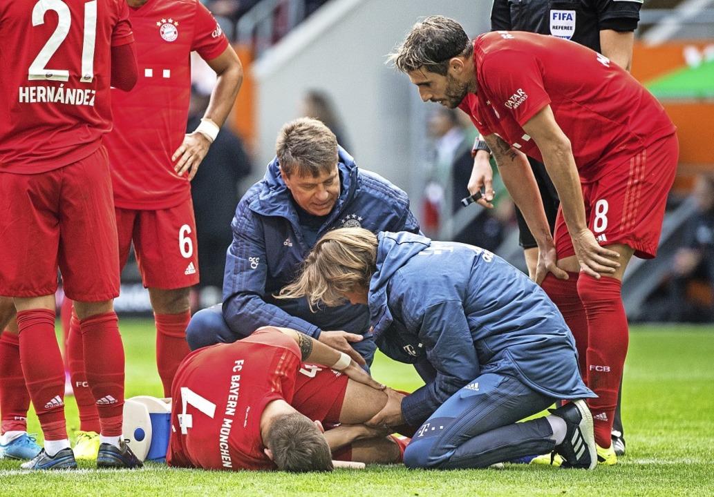 Helfer kümmern sich um Niklas Süle wäh...r Partie der Bayern beim FC Augsburg.   | Foto: Matthias Balk (dpa)