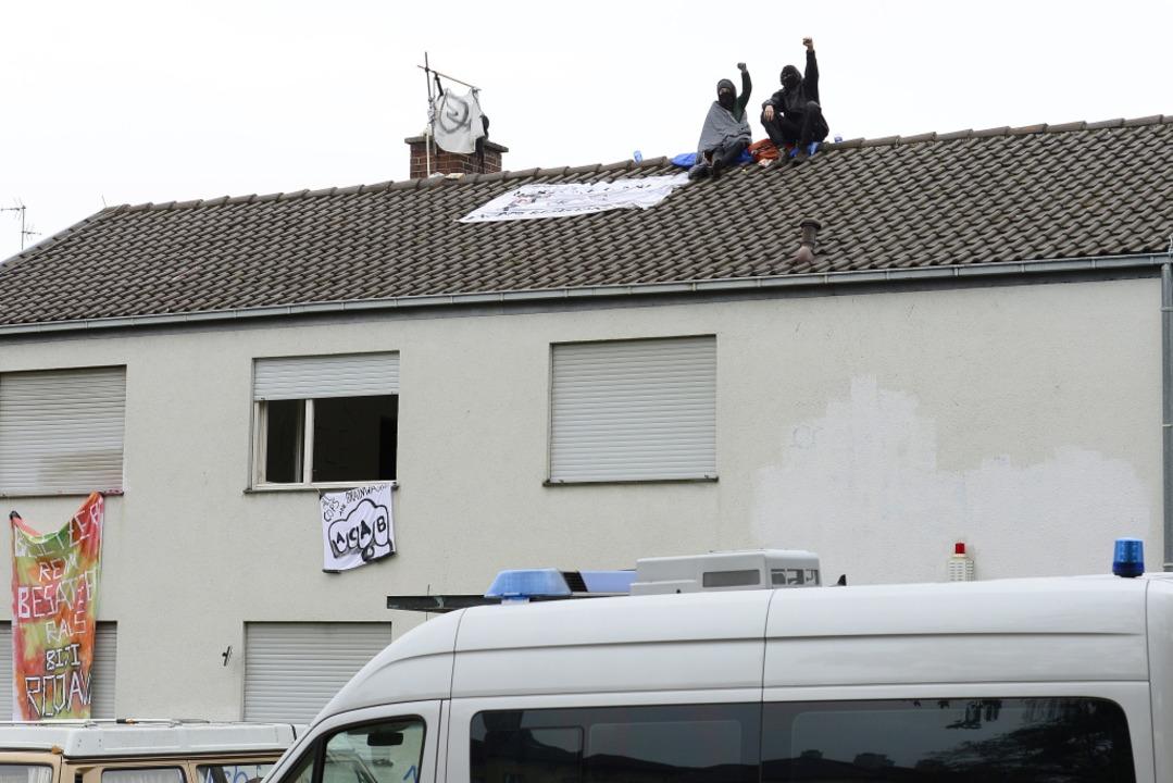 Zwei Hausbesetzer auf dem Dach des bes...Montagvormittag die Hände in die Höhe.  | Foto: Ingo Schneider