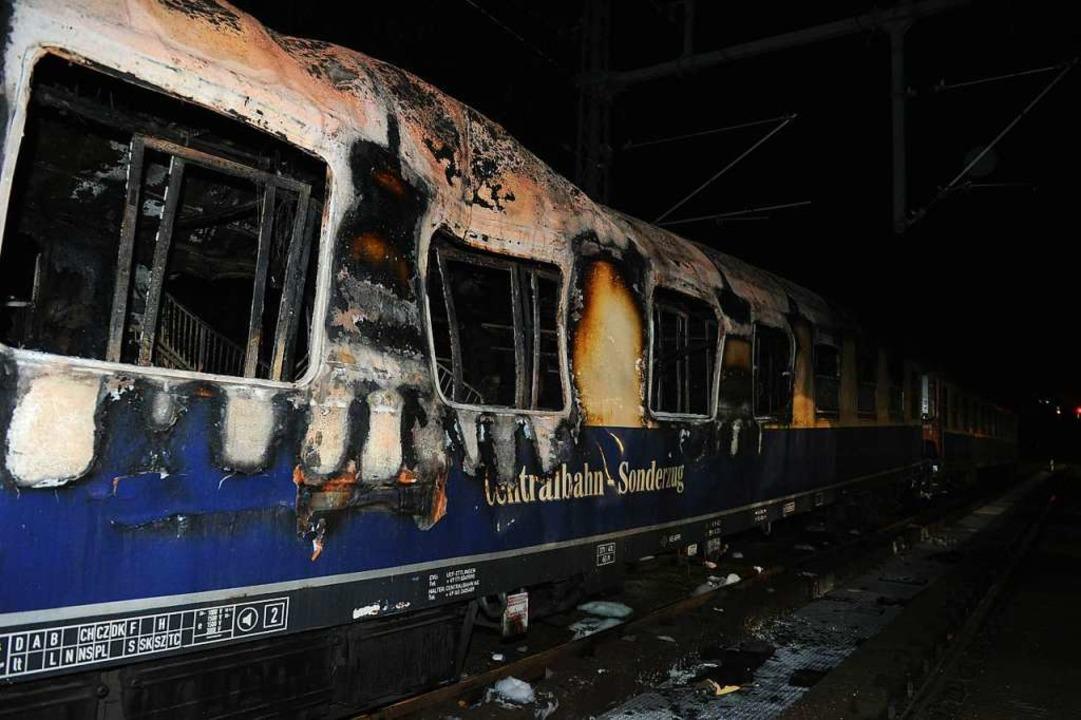 Der ausgebrannte zweite Waggon des SC-... nehmen den Wagen nun in Augenschein.   | Foto: spreepicture/Bild