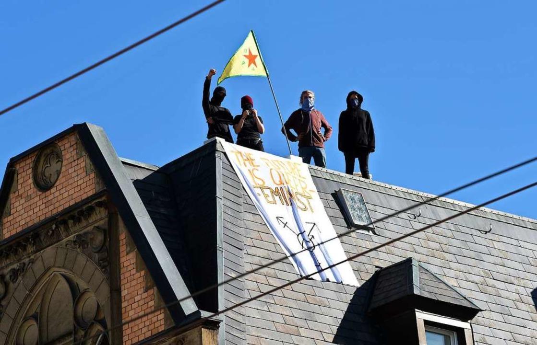 Besetzer stehen am Samstag auf dem Dach des Haus Kronenstraße 21  | Foto: Rita Eggstein