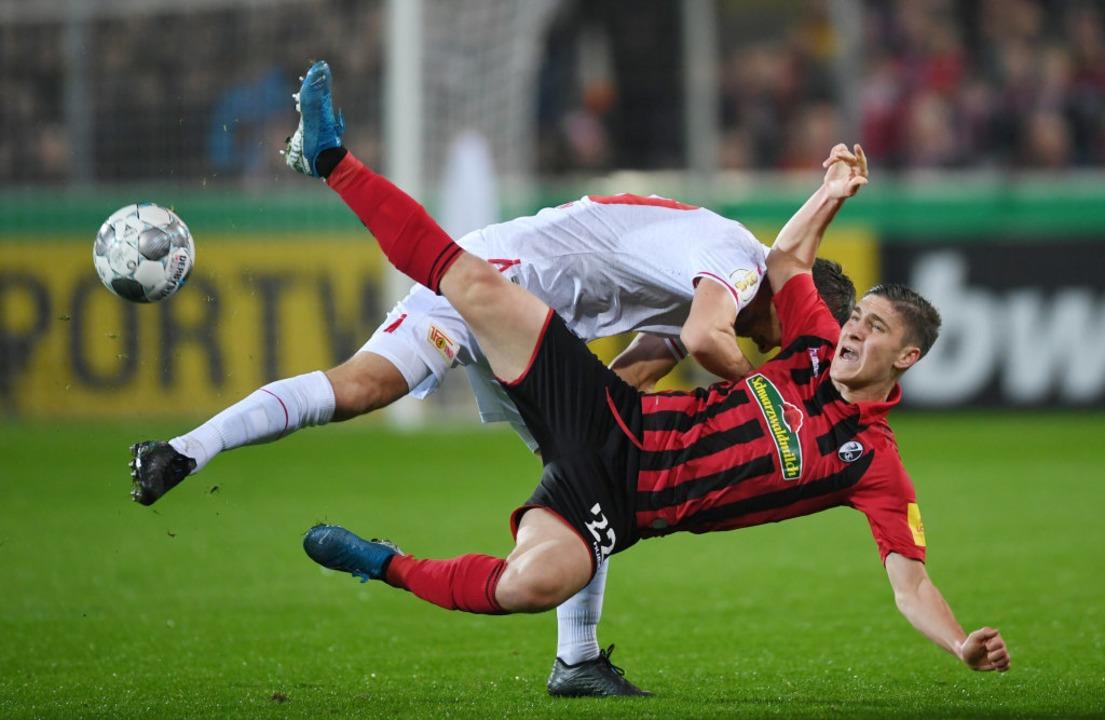 Michael Parensen (o) von Berlin und Ro... (u) von Freiburg kämpfen um den Ball.  | Foto: Patrick Seeger (dpa)