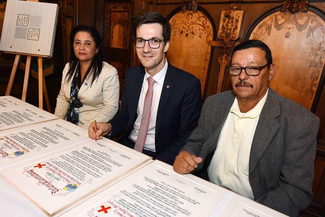 Oberbürgermeister Martin Horn (Mitte) ...d Reyna Hernandez offiziell besiegelt.  | Foto: Rita Eggstein