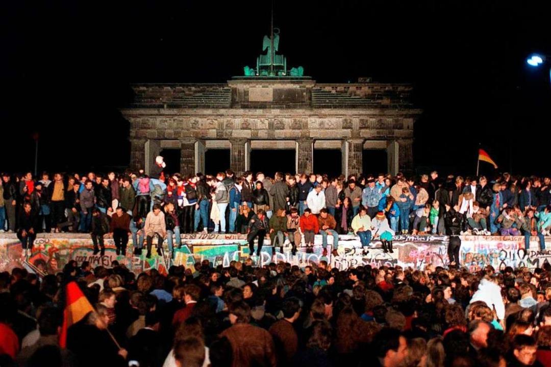 Jubelnde Menschen auf der Berliner Mauer am Brandenburger Tor (Archivfoto)  | Foto: Wolfgang Kumm (dpa)