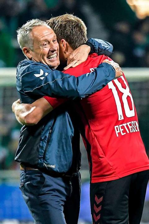 Große Freude: Christian Streich umarmt Nils Petersen nach dem Spiel.  | Foto: Axel Heimken (dpa)