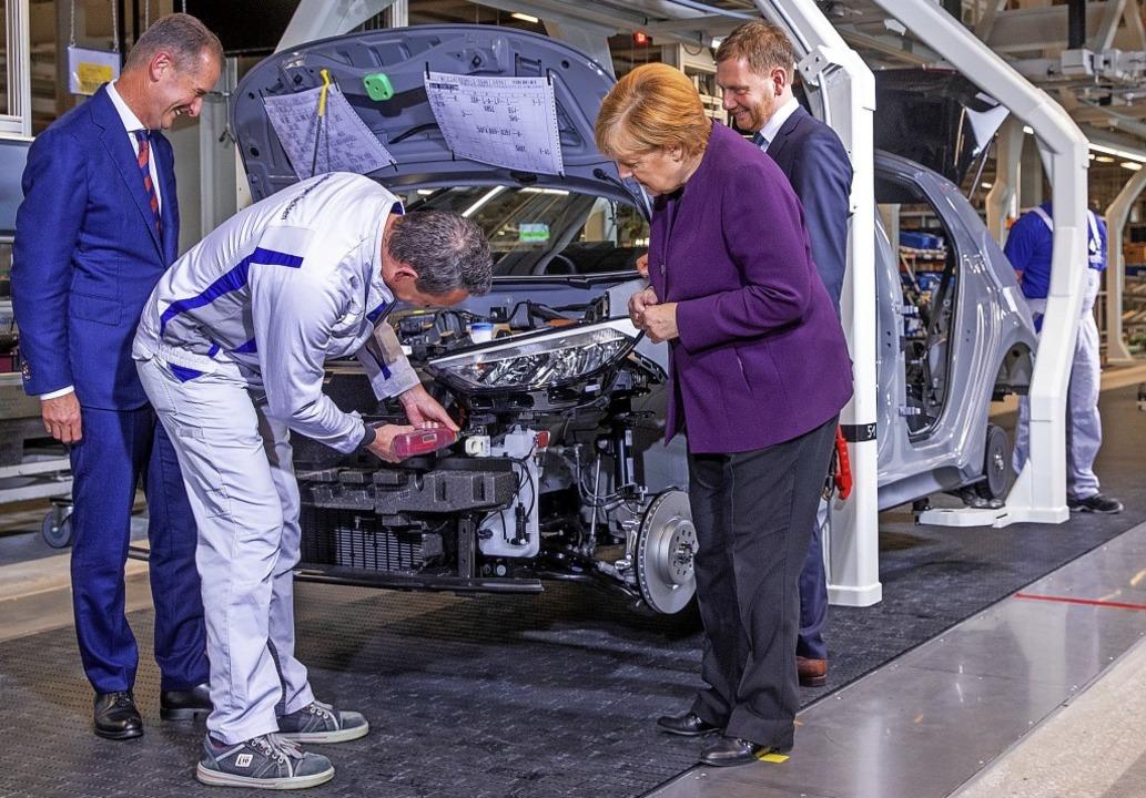 Kanzlerin Angela Merkel   mit VW-Konze...band für die Montage des Elektroautos.  | Foto: Jens Büttner (dpa)