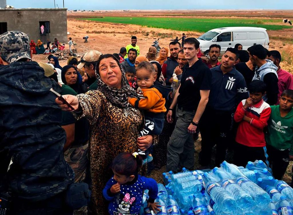 Menschen, die vor dem Einmarsch der tü...nd, werden mit Lebensmitteln versorgt.  | Foto: Carol Guzy (dpa)