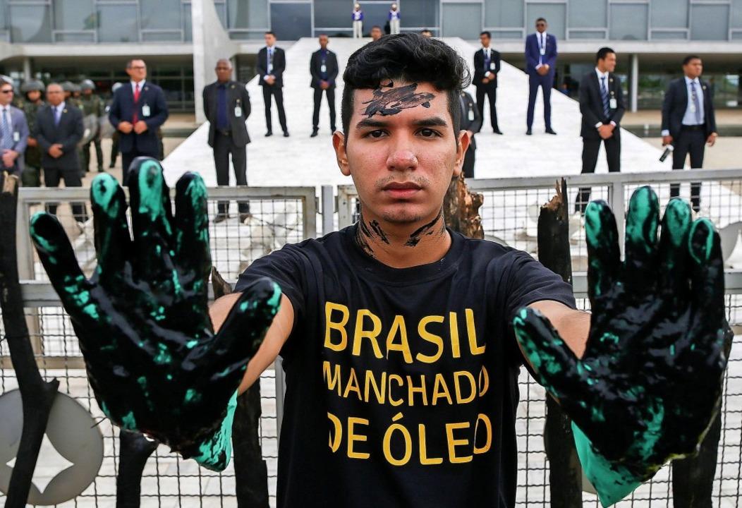 Ein Aktivist von Greenpeace protestiert gegen die Tatenlosigkeit der Regierung.  | Foto: SERGIO LIMA (AFP)