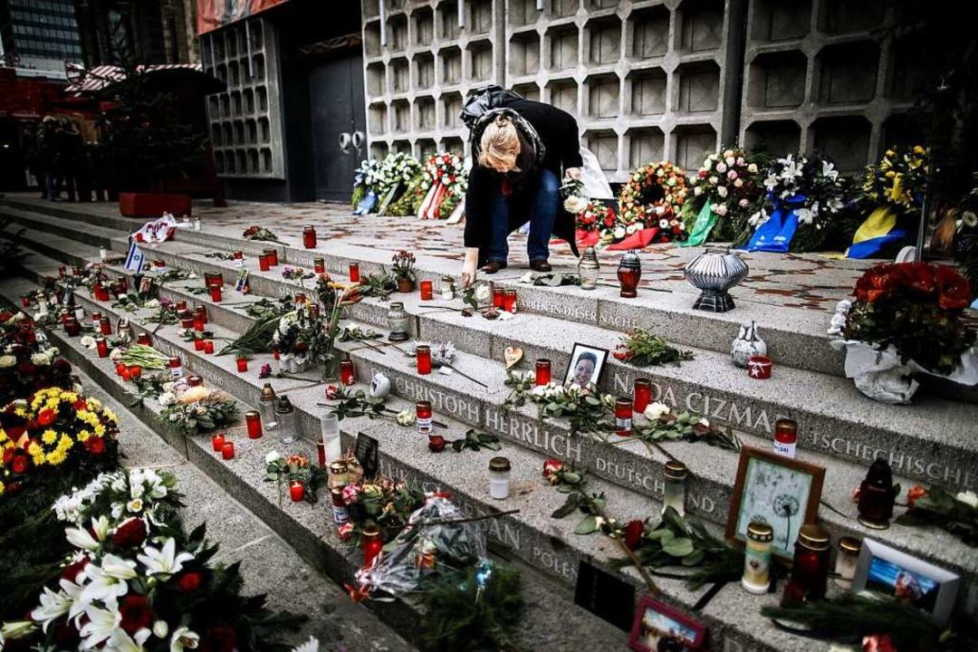 Eine Frau legt am Breitscheidplatz am Mahnmal eine Rose ab. (Archivbild)  | Foto: Carsten Koall