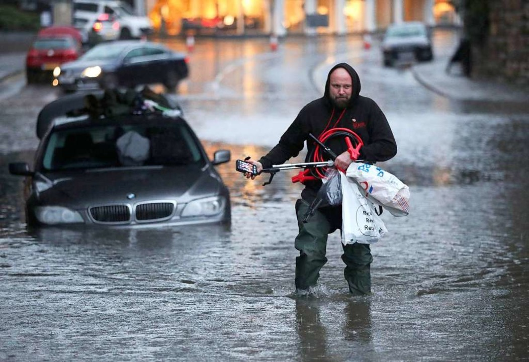Ein Mann watet durch eine überflutete ...nstände aus seinem Auto gesammelt hat.  | Foto: Danny Lawson (dpa)