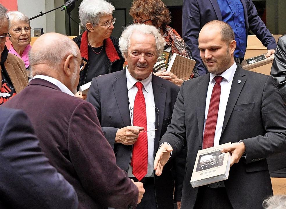 Wolfram Wette (Mitte) und Oberbürgerme...m Geschwister-Scholl-Gymnasium Bücher.  | Foto: Klaus Riexinger