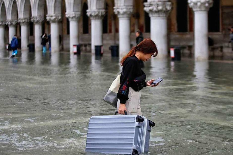 Eine Touristin trägt ihr Gepäck durch das Hochwasser auf dem Markusplatz. Die Flut erreichte am späten Dienstag einen Höchststand von 187 cm. Der Bürgermeister von Venedig spricht von einer «Katastrophe... (Foto: Luca Bruno (dpa))