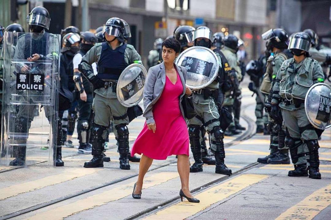 Eine Frau in pinkem Kleid geht an Poli...e der Pekinger Regierung demonstriert.  | Foto: Ng Han Guan (dpa)