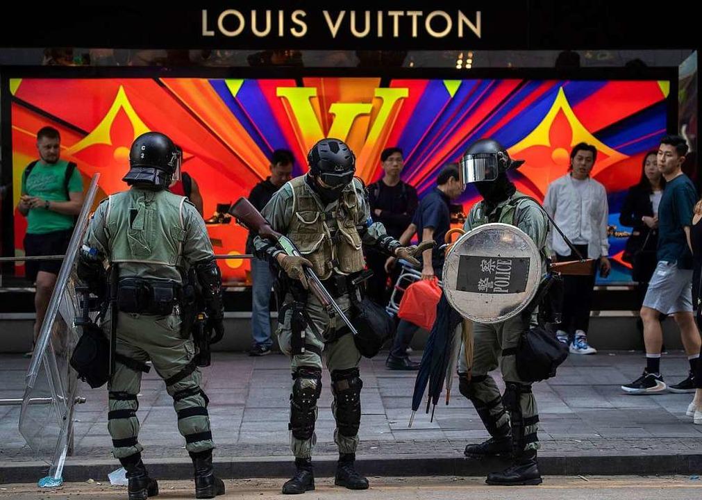 Polizisten sammeln vor einem Geschäft ...gierungskritischen Demonstranten, ein.  | Foto: Ng Han Guan (dpa)