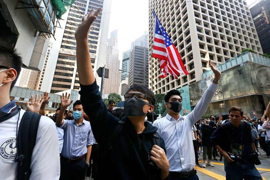 Demonstranten mit Mundschutz heben ihr...end eines Protestes im Finanzdistrikt.  | Foto: Achmad Ibrahim (dpa)