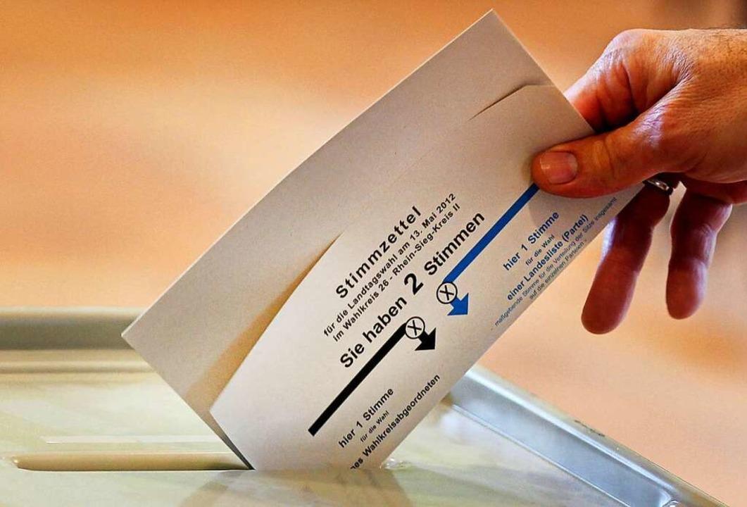 Eine Frau wirft einen Stimmzettel in d...ichtiger Bestandteil einer Demokratie.  | Foto: Oliver Berg (dpa)