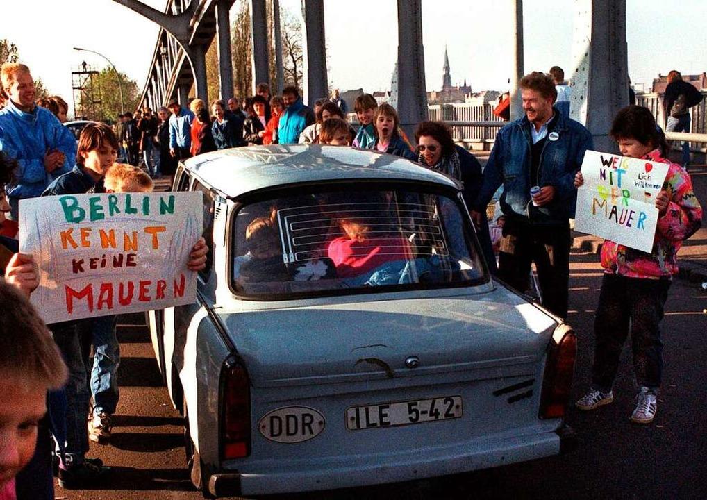 Ein Trabi aus dem Osten der Stadt wird...n mit selbstgemalten Plakaten begrüßt.  | Foto: dpa (dpa)