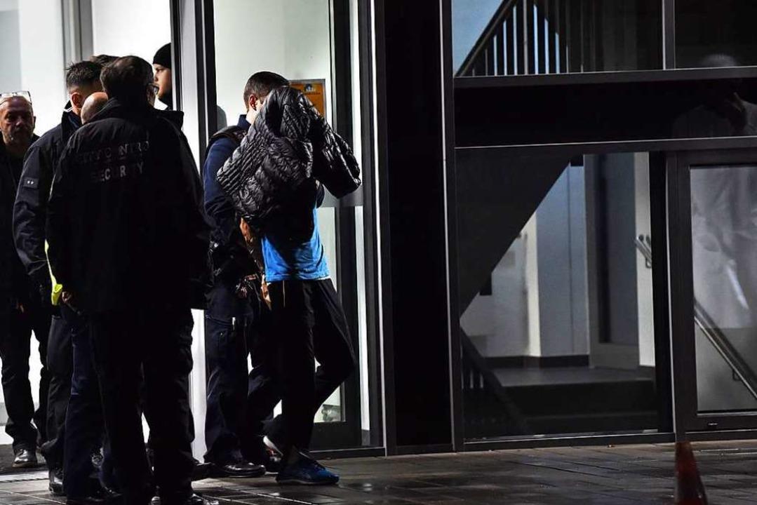 Polizisten führen nach den tödlichen Messerstichen einen Verdächtigen ab.  | Foto: Paul Zinken (dpa)